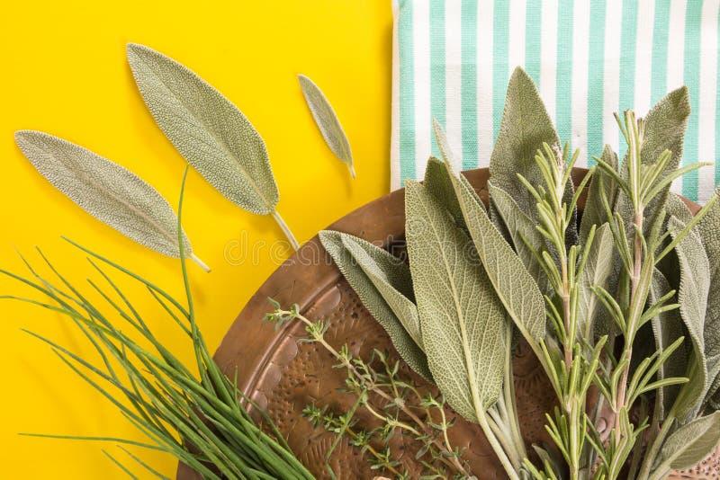 Vecchio piatto di rame con varietà di erbe fresche sull'asciugamano piegato a strisce blu e sul fondo giallo fotografia stock