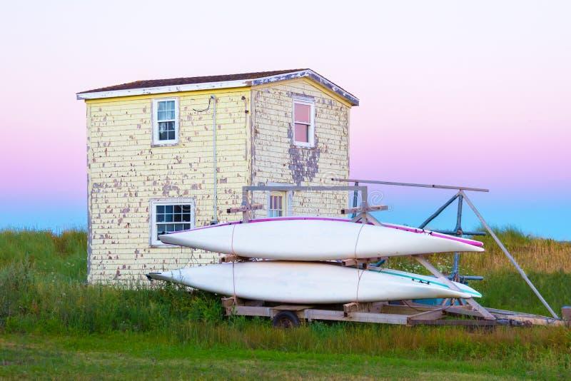 Vecchio piccolo cottage con la pelatura della pittura gialla con due canoe immagine stock libera da diritti