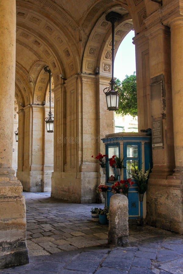 Vecchio piccolo negozio di fiore fra la colonna di bella costruzione immagini stock