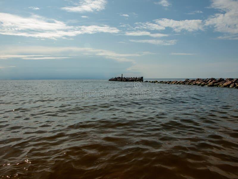 Vecchio pilastro di pietra nel mare immagini stock libere da diritti