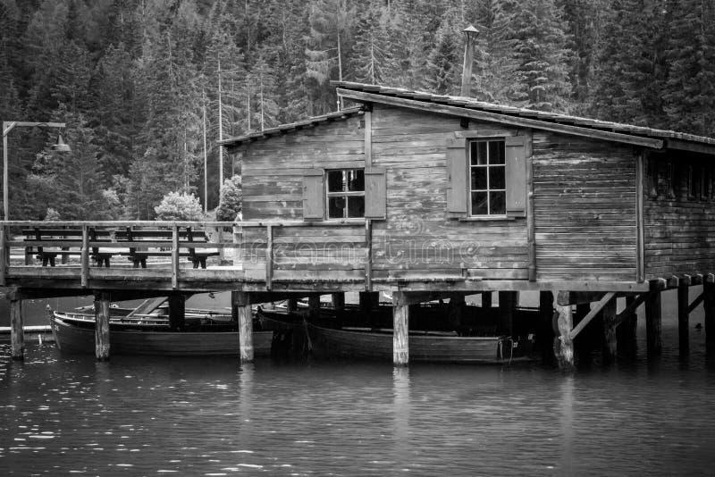 Vecchio pilastro nel lago di Braies in bianco e nero immagine stock