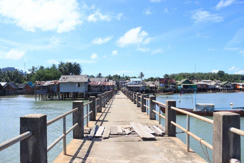 Vecchio ponte concreto per mettere in bacino il pilastro del villaggio del pescatore nella destinazione tranquilla del mare immagini stock