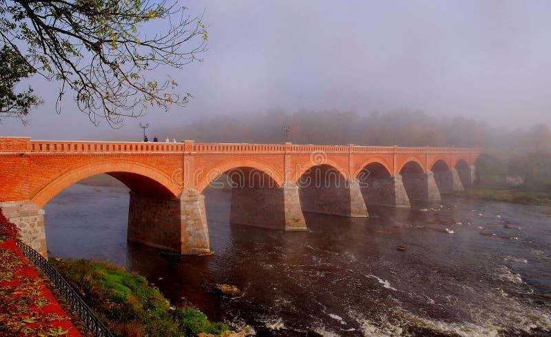 Vecchio ponte del mattone attraverso il fiume Venta fotografia stock