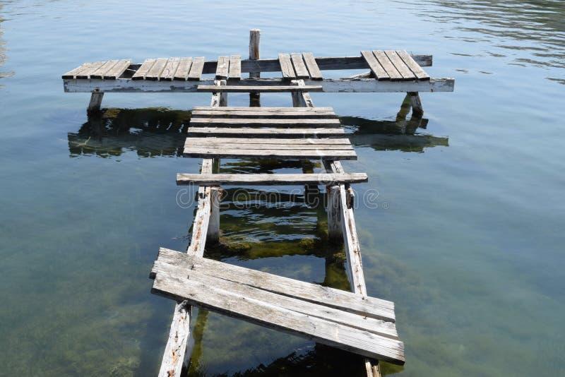 Vecchio ponte di barca marcio in una città fantasma immagini stock libere da diritti