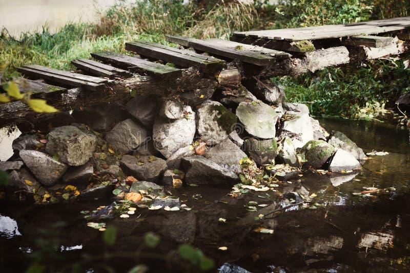 Vecchio ponte di legno abbandonato attraverso la corrente immagini stock