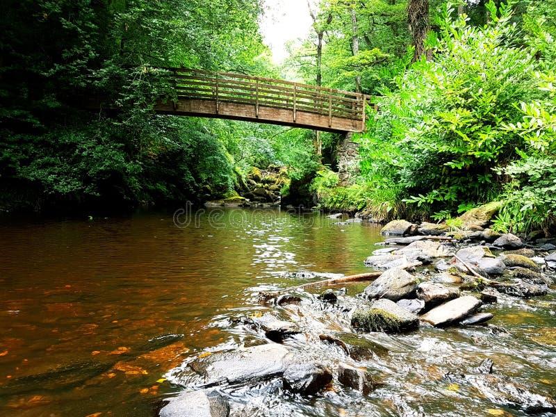 Vecchio ponte di legno sopra il fiume scorrente immagini stock