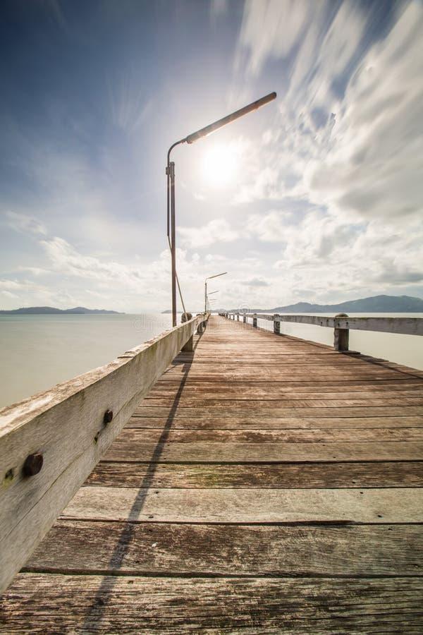 vecchio ponte di legno sul muoversi della nuvola e del mare immagine stock