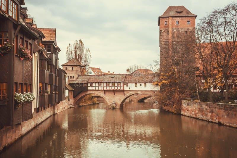 Vecchio ponte di pietra con la torre e case sopra un fiume dentro la città storica fotografie stock libere da diritti