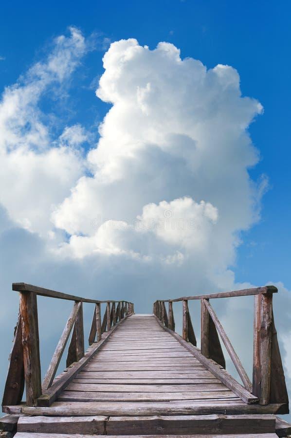 Vecchio ponticello di legno, cielo blu e nubi bianche immagine stock