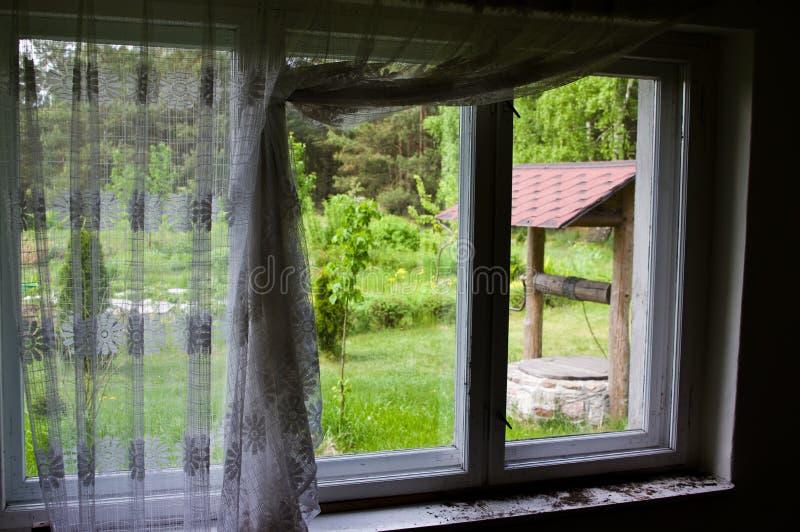 Vecchio pozzo visto attraverso una finestra rustica immagini stock