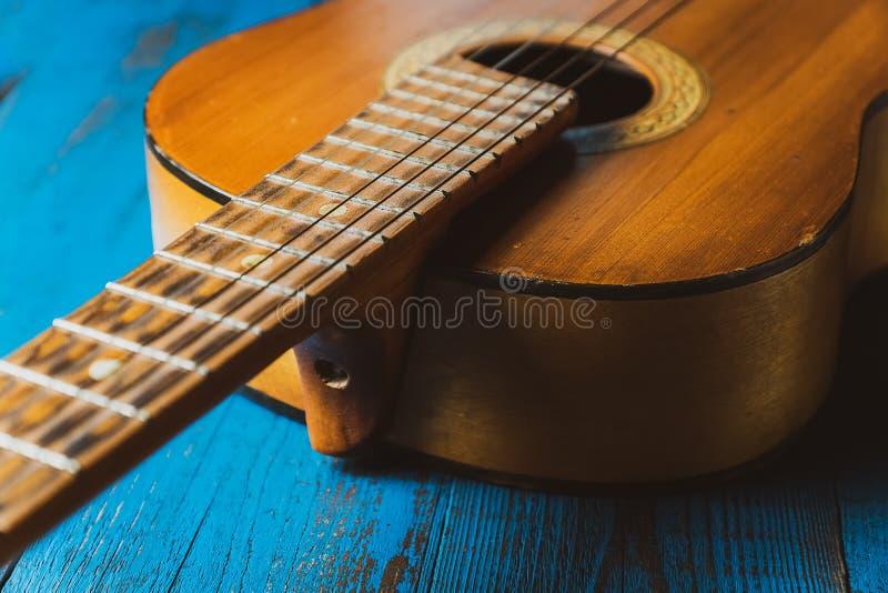Vecchio primo piano classico della chitarra, su fondo blu fotografia stock