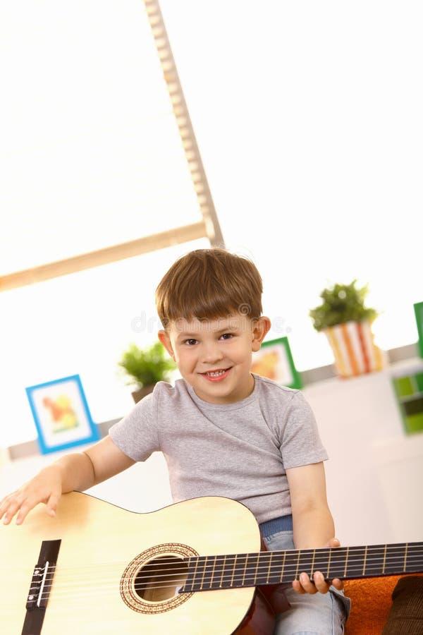 Vecchio quinquennale felice con la chitarra fotografia stock