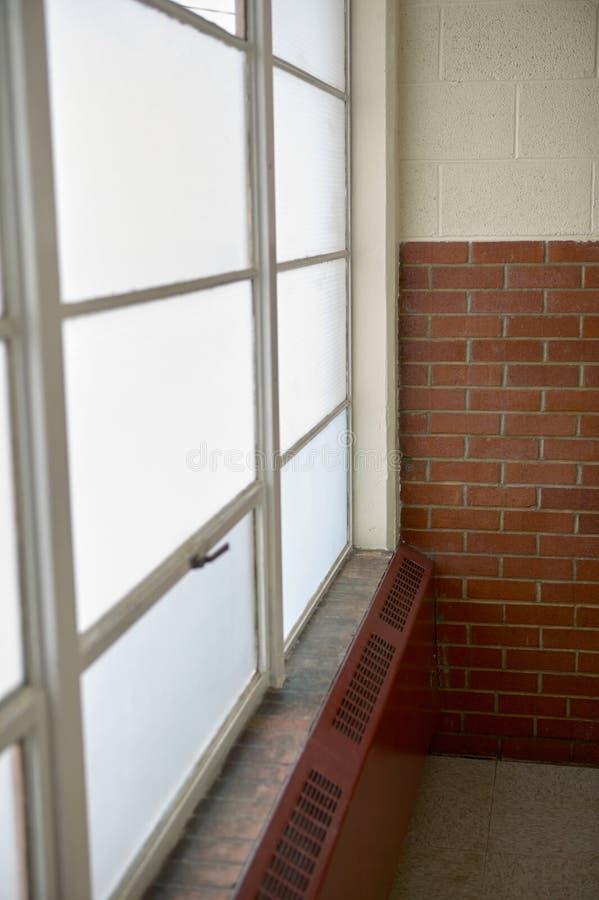 Vecchio radiatore sotto una finestra incorniciata metallo fotografie stock