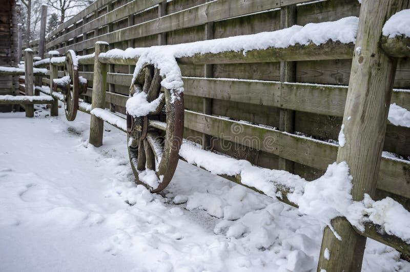 Vecchio recinto di legno decorato con le ruote d'annata dai carretti storici tradizionali, in un'iarda rurale immagine stock