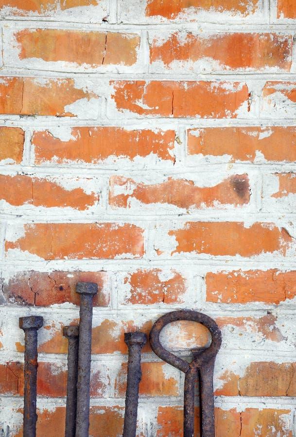 Vecchio residuo arrugginito del ferro che sta sui precedenti di un muro di mattoni immagini stock libere da diritti