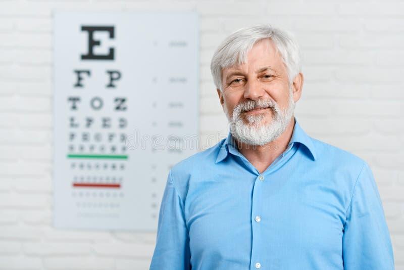 Vecchio restare paziente davanti alla tavola di ispezione visiva fotografie stock