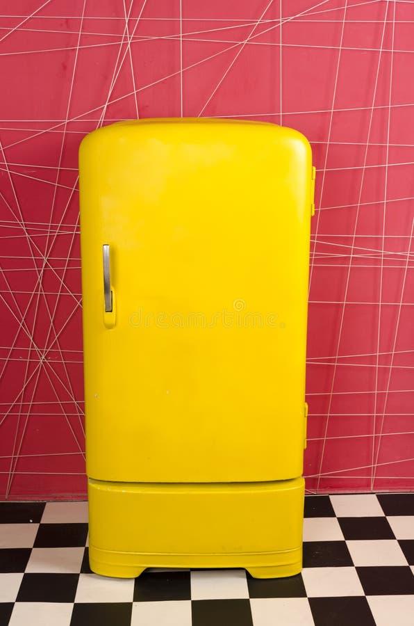 Vecchio retro frigorifero d'annata giallo su un fondo rosa immagine stock