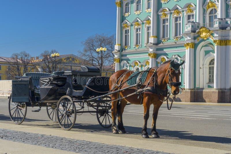 Vecchio retro trasporto davanti al Museo dell'Ermitage del palazzo di inverno sul quadrato del palazzo a St Petersburg, Russia Ve fotografia stock libera da diritti