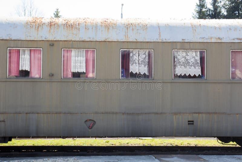 Vecchio retro vagone d'annata grigio d'annata che sta sulle rotaie fotografia stock
