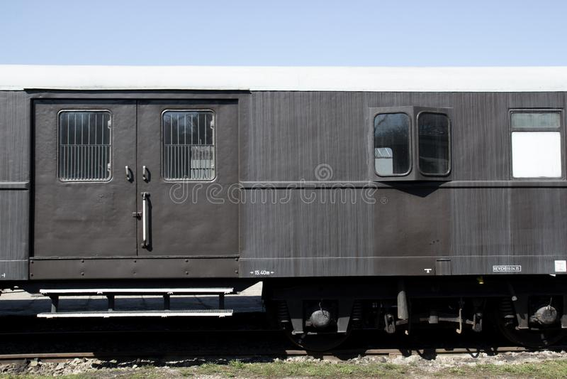 Vecchio retro vagone d'annata grigio che sta sulle rotaie sui precedenti di cielo blu fotografie stock