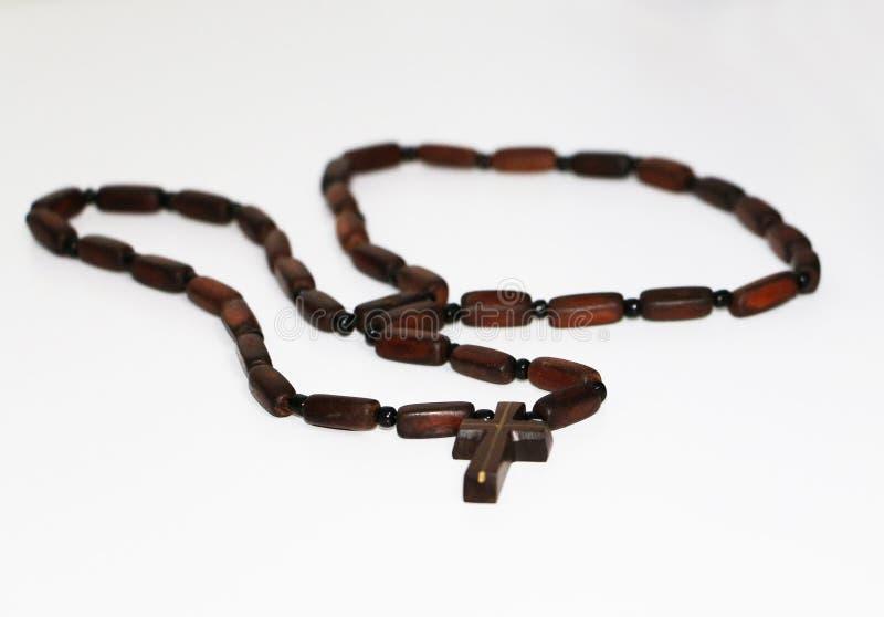 Vecchio rosario con le perle di legno poste, il pendente e la catena trasversali cristiani su fondo bianco vago con area in bianc immagine stock