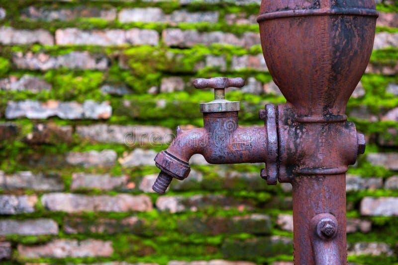 Vecchio rubinetto arrugginito con il vecchio muro di mattoni fotografia stock