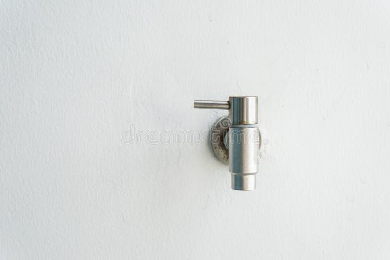 Vecchio rubinetto d'argento arrugginito sulla parete bianca fotografie stock libere da diritti
