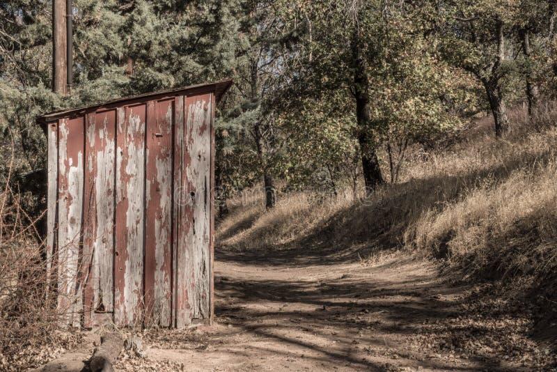 Vecchio, sbucciando pittura rossa su piccolo, legno fuori che costruisce sul percorso rurale immagine stock libera da diritti