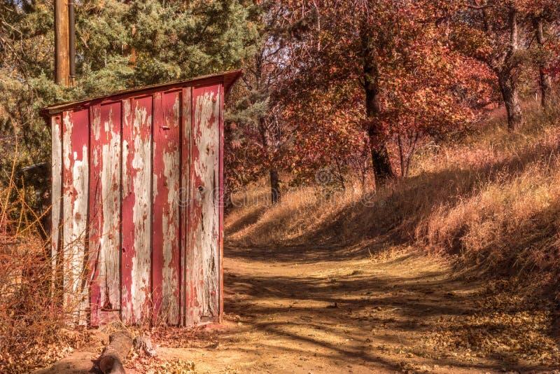 Vecchio, sbucciando pittura rossa su piccolo, legno fuori che costruisce sul percorso rurale fotografia stock