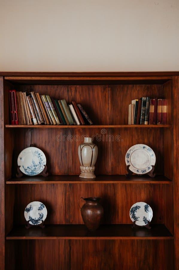 Vecchio scaffale per libri di legno con i piatti, il vaso ed il barattolo delle porcellane immagine stock libera da diritti