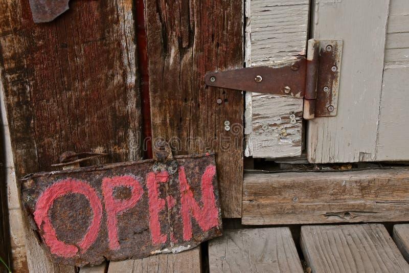 Vecchio segno di legno APERTO da una porta di pelatura rustica con una cerniera arrugginita fotografie stock libere da diritti