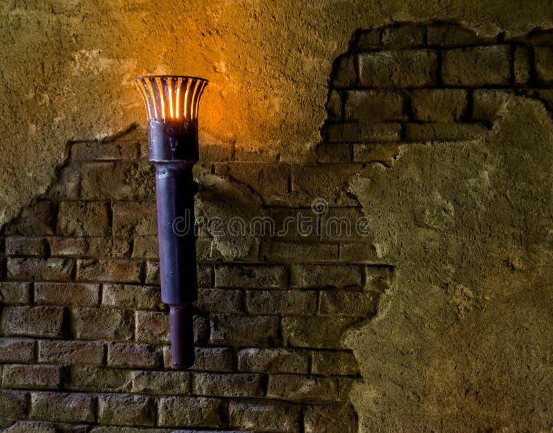 Vecchio sguardo e torcia accesa che appendono su una parete di pietra, interni medievali del metallo fotografie stock libere da diritti