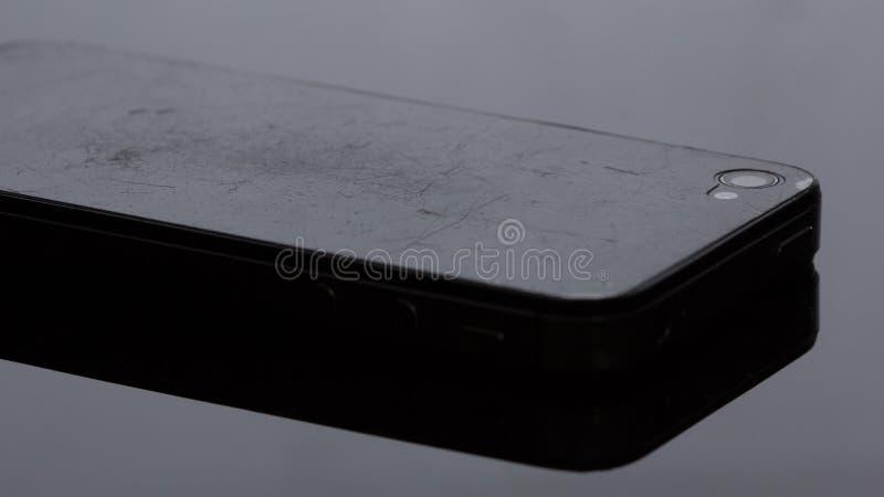 Vecchio smartphone che il film ha graffiato Su fondo nero immagine stock libera da diritti