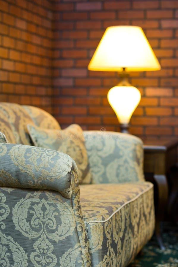 Vecchio sofà in un salone con la decorazione rossa del muro di mattoni immagini stock libere da diritti