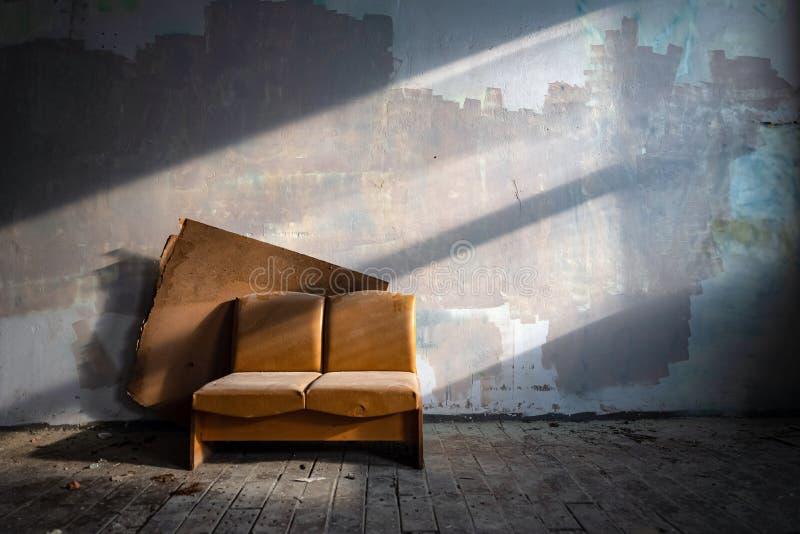 Vecchio strato di cuoio nel lato abbandonato della costruzione della fabbrica acceso dal sole Mobilia rustica in casa frequentata fotografia stock