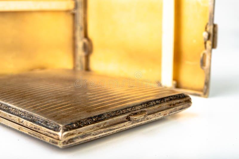Vecchio tabacco-tubo del metallo su una tavola bianca Le sigarette antiquate imballano fotografia stock libera da diritti