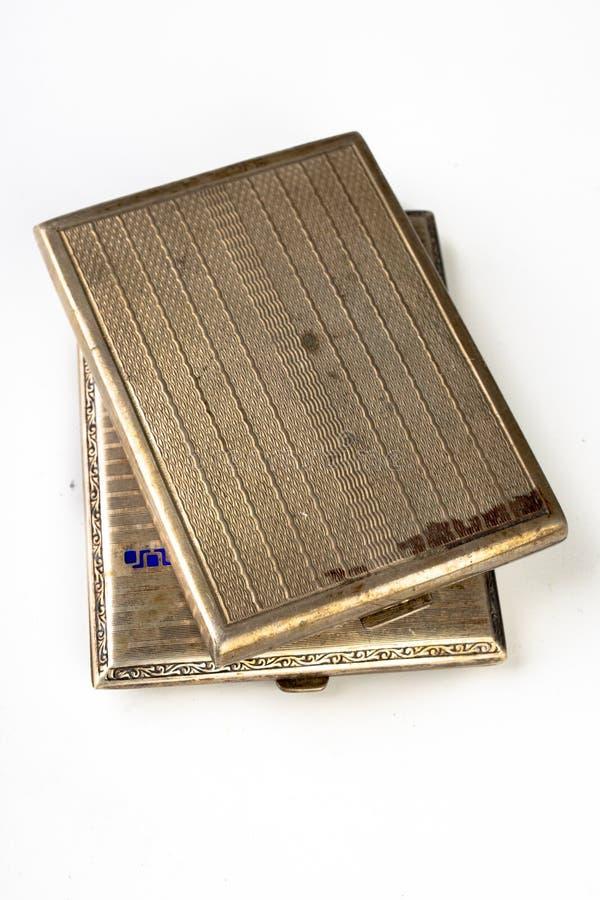Vecchio tabacco-tubo del metallo su una tavola bianca Le sigarette antiquate imballano immagine stock