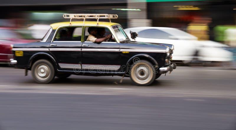 Vecchio taxi nero e giallo tradizionale nel movimento in Mumbai, India immagini stock libere da diritti