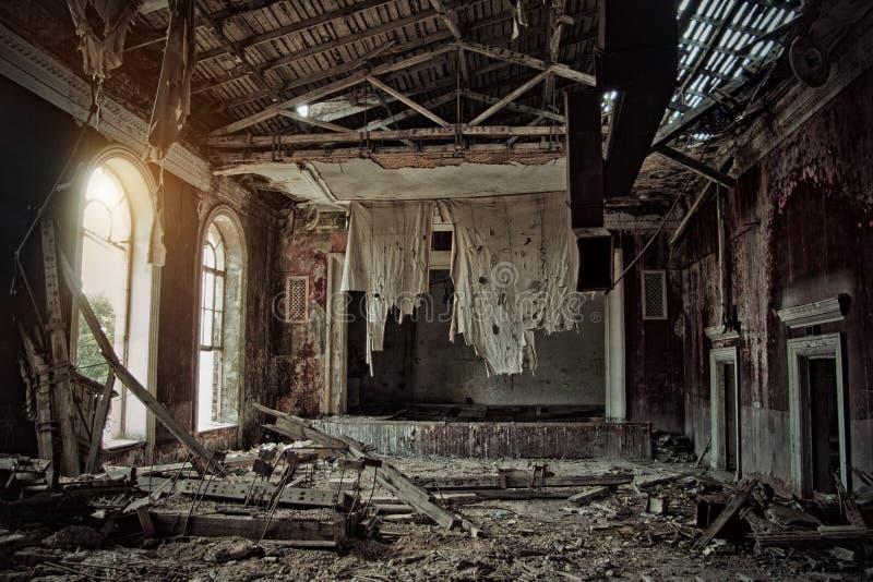 Vecchio teatro frequentato rovinato marcio abbandonato terrificante, una tenda stracciata fotografie stock