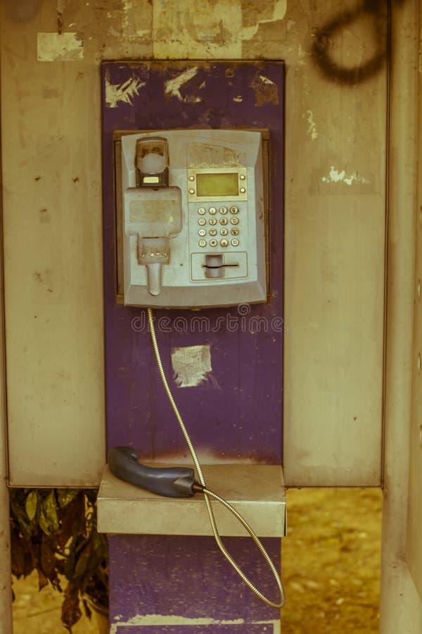 Vecchio telefono a gettone fuori servizio nella città fotografie stock