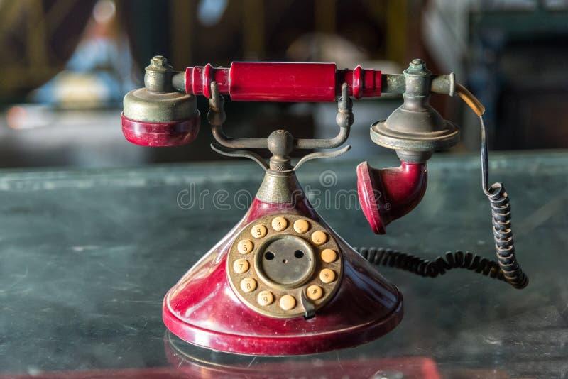 Vecchio telefono rosso con il quadrante rotatorio sulla tavola di vetro fotografia stock libera da diritti