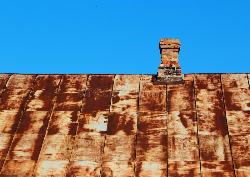 Vecchio tetto arrugginito del metallo con il camino del mattone contro cielo blu fotografia stock