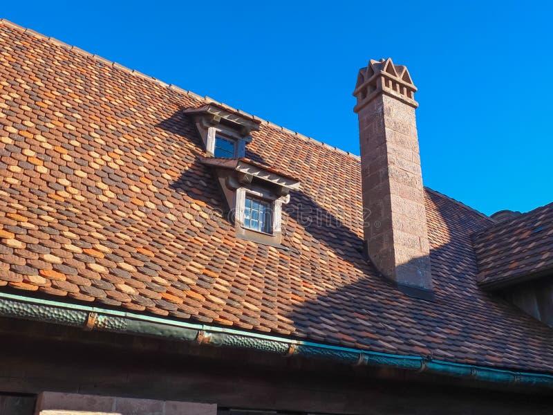 Vecchio tetto piastrellato con i camini e gli abbaini su cielo blu fotografia stock libera da diritti