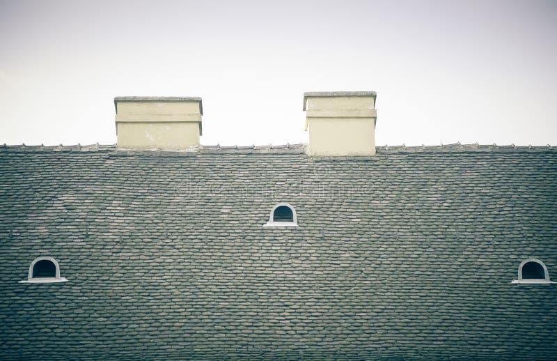 Vecchio tetto piastrellato con i camini e gli abbaini sul fondo del cielo blu fotografia stock