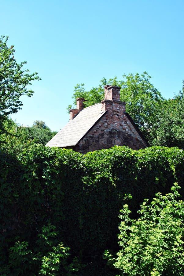Vecchio tetto rosso della casa con mattoni a vista con due camini sulla cima nascosta in giardino verde con l'alta parete del rec fotografia stock libera da diritti