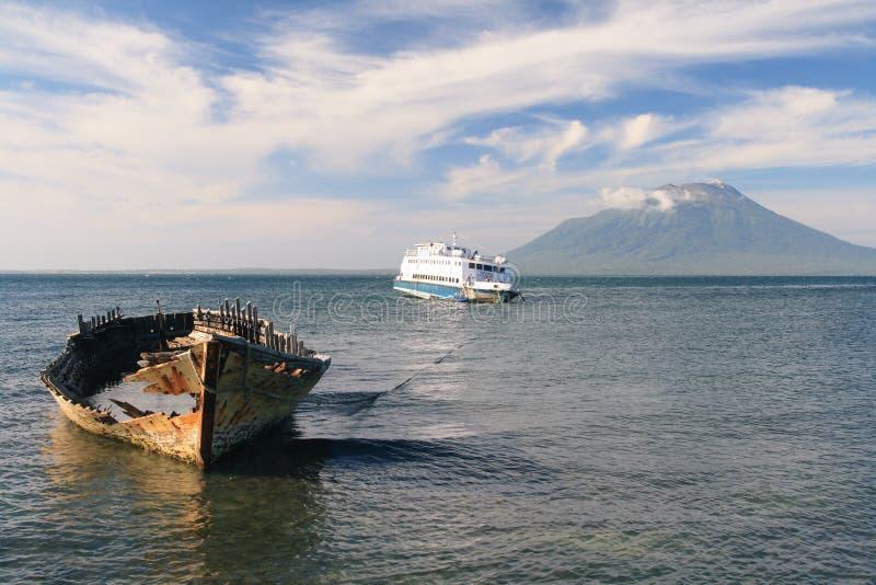 Vecchio traghetto di legno davanti ad un vulcano, Indonesia fotografie stock