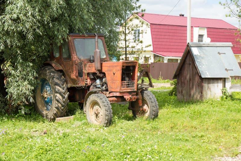 Vecchio trattore arrugginito rosso sulla campagna immagini stock