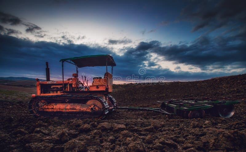 Vecchio trattore arrugginito in un campo sul tramonto Immagine di HDR immagine stock libera da diritti