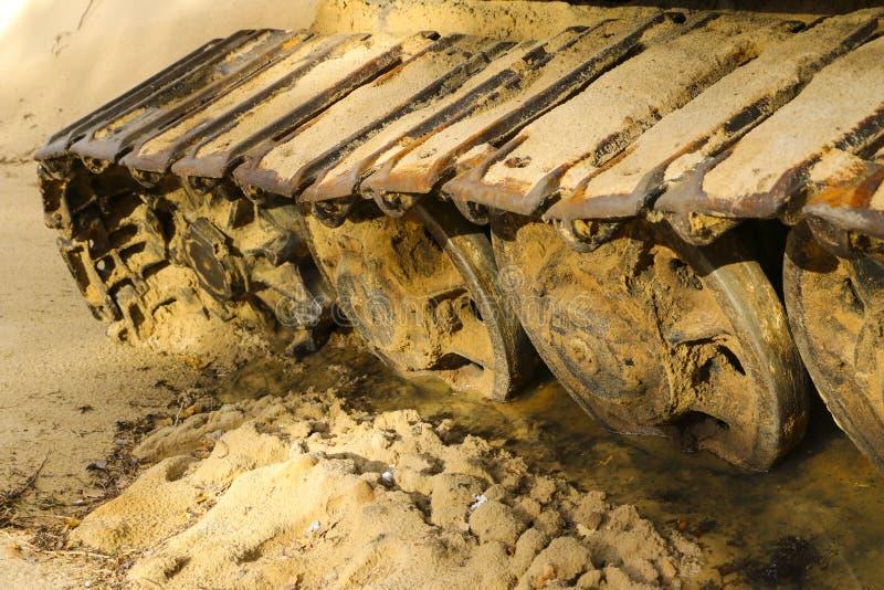 Vecchio trattore a cingoli del ferro in sabbia bagnata Ruote e nastro d'acciaio arrugginiti di grande bulldozer, carro armato, es immagine stock libera da diritti