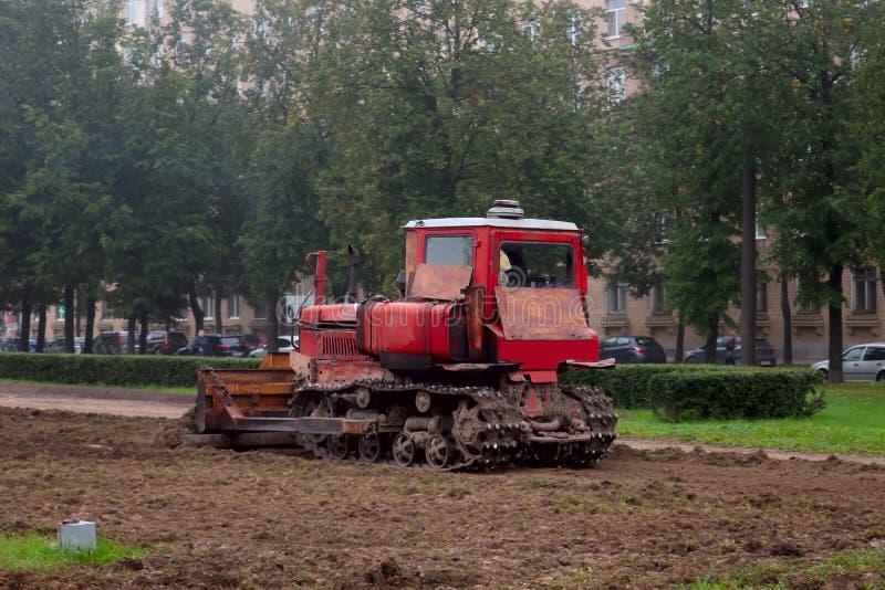 Vecchio trattore a cingoli rosso arrugginito che livella la terra fotografie stock libere da diritti